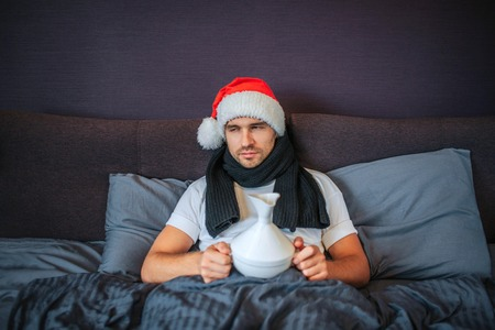 Sick and very ill young man sits on bed. He is covered with blanket. Guy looks to sisw. He holds white inhaler. He is going to do procedures. Mans neck has scarf around. Christmas hat is on head.