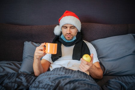 Sick young man sits on bed. He covered with blanket. Guy holds cup in one hand and lemon in another one. He looks at citrus. Also guy has scarf around his neck and Christmas hat on head.