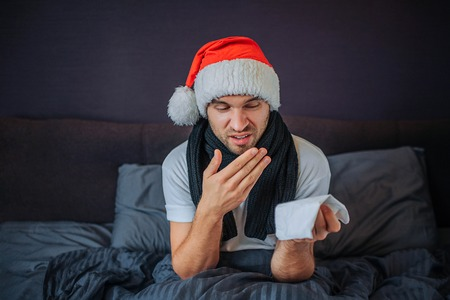 Sick young man in red hat sits and look on tissue he has in hand. He is going to sneeze so man wants to cover up mouth. Guy stays in bed. He feels very ill.