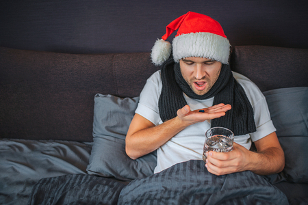 Picture of sick young man going to swallow pills he has on hand. Guy looks at them and shrinks. He has glass of water in another hand. Young man has scarf around neck and Christmas hat on head. 版權商用圖片