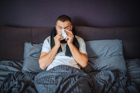 Sick young man sits on bed. He is covered with blanket. Guy sneezing into tissue. He suffers. Young man feels terrible. He is concentrated on sneezing. Stock fotó