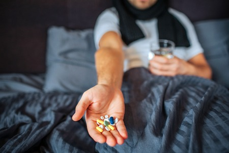 Cut view of young man sitting on bed and holding lots of pills on hand. Guy has glass of water as well. Sick man has scarf around neck. 版權商用圖片