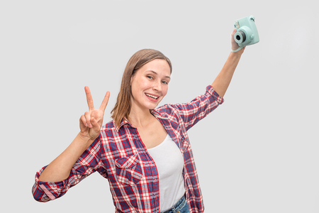 Young woman holding blue camera in hand and stretch arm up. She poses and smiles. Woman looks straight. She shows piece symbol with fingers. Isolated on grey background. Stockfoto