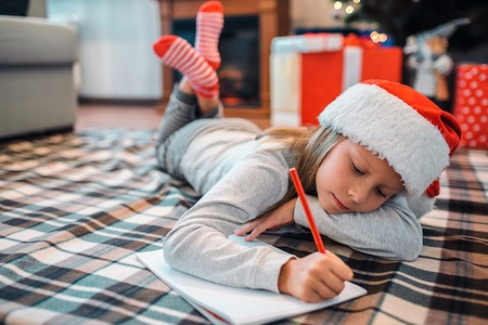 Calm and peaceful girl lying on floor and writing letter. She keeps her legs crossed and holding head on hand. Child is in room alone. She wears Christmas hat.