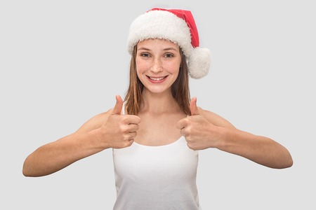 Positive young woman looks on camera and shows her big thumbs up. She wears white t-shirt and red Christmas hat. Model smiles. Isolated on grey background.