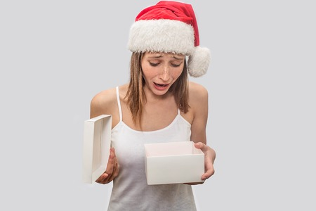 Wondered and upset younf woman holds opened white box with present. She looks inside of it. Model is distressed. She is unhappy. Isolated on grey background.