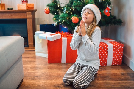 Small girl sitting on her knees and praying. She keeps eyes closed and holds hands togther. Child wishing and saying thanks. There are boxes wth gifts and Christmas tree behind her. Reklamní fotografie