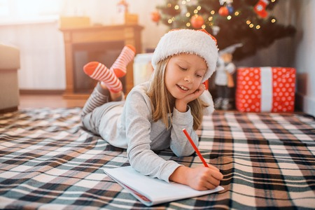 Delightful child is lying on blanket and writing letter. She holds another hand under chin and keeps legs crossed. Girl is alone in room. There are Christmas tree behind her.