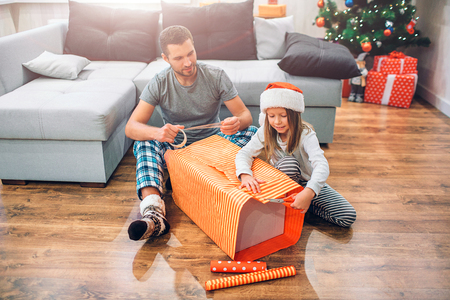 Young man sitting on floor with small girl and packing big box of present. They are concentrated on work. Girl cuts part of useless paper. Young man looks at her and holds tape in hands. 写真素材