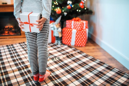 Cut view of small girl standing back to camera. She hides box of white present. Girl stands in front of Christmas tree with gifts.