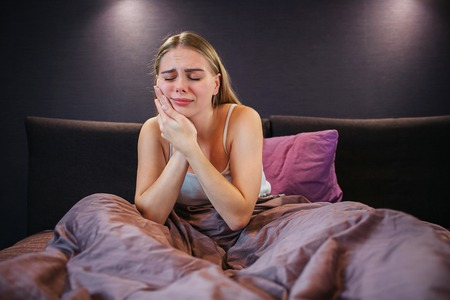 Young woman suffers from toothache. She holds both hands on cheek together and keeps eyes closed. It is painful. Model sits on bed. Her legs are covered with blanket.