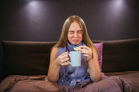 Beautiful young woman shrinks from sour lemon. She holds piece of it in one hand and cup of hot tea in another one. Woman suffers.