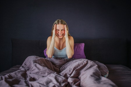 Young woman suffers from headache. She screams out loud. Model holds hands close to forehead. Her legs are covered with blanket. She sits on bed. Young woman is alone. Stock fotó