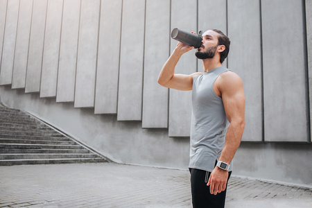 Muscled and well-built young man stands and drinks water from black bottle. He looks up. Guy stands close to concrete walls. Stock Photo