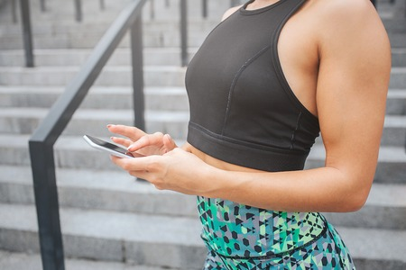 Cut view of young womans chest wearing sports bra. Model holds phone in hands and uses it. She uses it. Woman stands on steps. She is in very good shape.