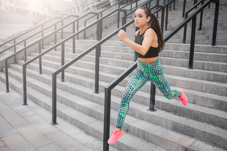 Picture of fast running model. She does it on steps. Young woman helps herself with hands. She runs as fast as she can. Young woman poses on camera in this way.