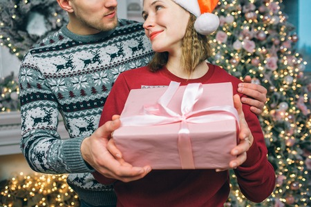 Lovely and nice couple stand together and look at each other. They smile. People hold present together. There is Christmas tree behind them. 写真素材