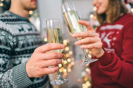 Cut view of young man and woman standing in front of each other. They wear Christmas sweaters. Couple holds glasses of champaigne. She smiles. 写真素材