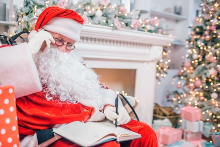 Concentrated and thoughtful man in Santa Claus costume sits at fireplace and Christmas tree. He holds phone t ear and whites down in notebook.