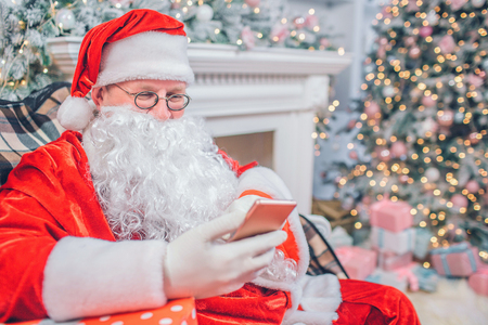 Busy Santa Claus sits and look at phone he holds in hands. Man is alone in festive room. He sits at fireplace and Christmas tree. Imagens