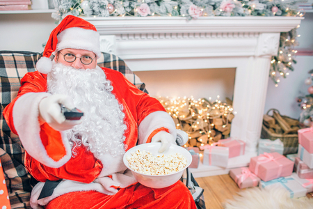 Excited Santa Claus sits at fireplace and holds remote control. Man holds bowl of popcorn. He is happy.