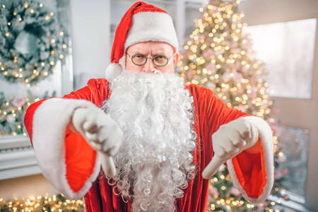 Angry old Santa Claus looks on camera and shows big thumbs down. Man is mad. He is in room alone. Stock Photo