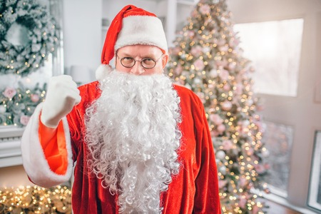 Picture of Santa Claus stands and looks on camera. He shows fist. Man threatens. He is in festive room.