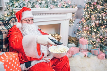 Satisfied and happy man in Santa Claus costume sits and uses remote control. He has bowl of popcorn in another hand. There are fireplace and Christmas tree behind man.