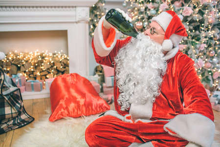 Santa Claus sits on floor and drinks alcohol from bottle. He is drunk. His red bag is at fireplace. Man alone in room. Stockfoto