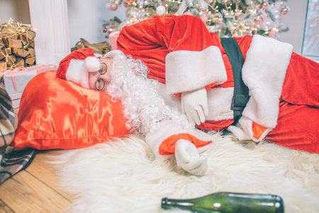 Drunk Santa Claus lying on floor and sleeping. His bag is under head. Bottle lying on carpet.