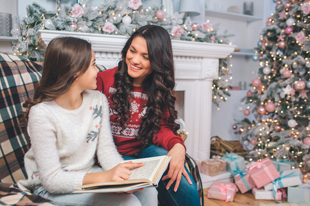 Pleasant young woman look at her daughter. They smile to each other. Family sits in decorated room with fireplace and Christmas tree. They look festive. Girl holds white book.