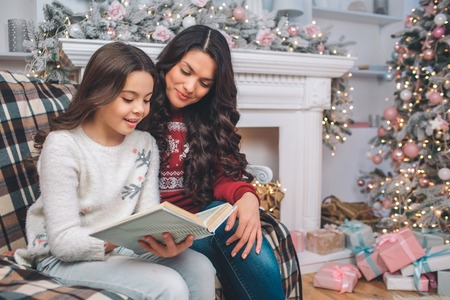 Mother sittng together with daughter and look at book. They read it. Girl holds it with both hands. They are in decorated room. There are Christmas tree and fireplace behind them.