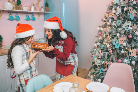 Nice young woman and girl stands and holds pie together. They smell it. People smile. They wear aprons and festive clothes with red hats.