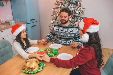 Nice and delightful members of family sitting at table and playing. They hold each others hands and keep eyes closed. They pray before eating festive food.