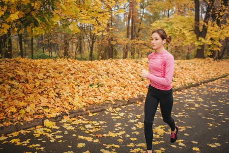 Female jogger runs on road in park. She is alone. Model training. It is autumn outside.