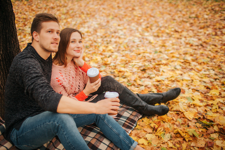 Beautiful couple sitting together and look in one direction. They hold cups of coffee. He embrace her. They sit in park. 写真素材