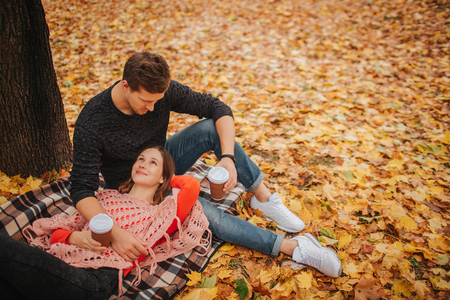 Lovely picture of young couple in park. Woman lying on blanket and look at guy. Man sits and looks at woman. They have cups of coffee.