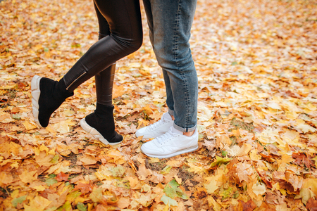 Cut vuew of young man and woman legs. He stands on two. She holds one feet up. They stand on yellow leaves. Stockfoto