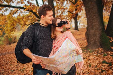 Handsome man stands besides woman and hold binoculars. She looks in it. They hold map together. People are in park.