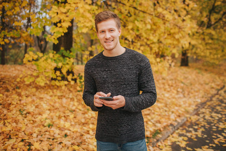 Cheerful and positive young man stands and looks on camera. He looks on camera and smiles. Young man has phone in hands. Фото со стока