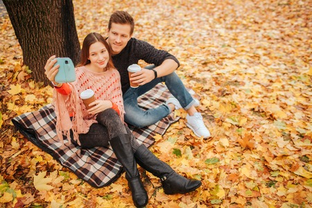 Nice and cheerful young man and woman sit on blanket and pose on camera. They have cups of coffee. Young woman holds blue camera. Banque d'images - 112532733
