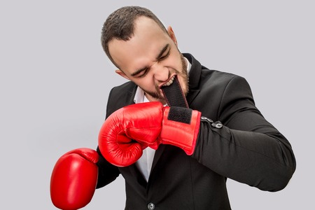 Serious and angry young man getting ready to fight. He holds clasp in mouth. Guy is concentrated. He wears suit and red box gloves. Isolated on white background. Reklamní fotografie