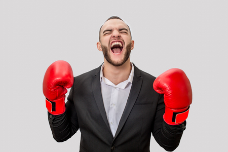 Picture of serious man in suit and red boxing gloves scremaing out loud. He looks up and keeps eyes closed. Isolated on white background.