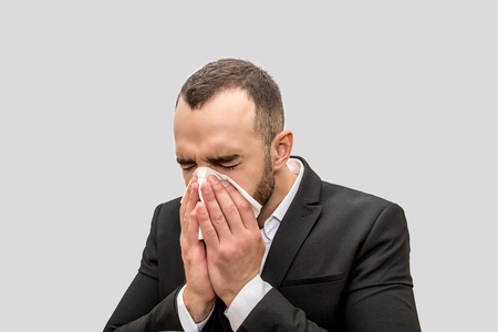 Young man sneez into white tissue. He keeps eyes closed. Young man is sick. Isolated on white background.