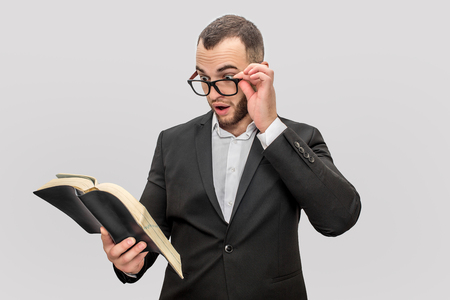 Wondered and excited young man hold book in one hand and glasses with another. He looks into book. Guy wears suit. Isolared on white background.