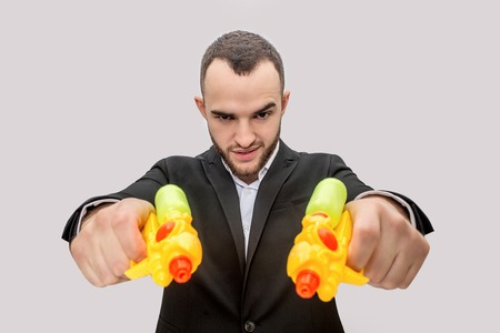 Dangerous young man in suit hold two water pistols in hands and direct them straight. He is angry and serious. Isolated on white background.