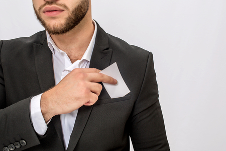 Cut view of young bearded man holds white piece of cloth. He put it into pocket. Young man wears suit. Isolated on white background. 免版税图像