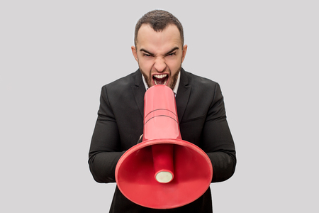 Angry young man screaming into red megaphone. He holds it with both hands. Young man is mad. Isolated on white background.