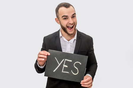 Happy young man in suit stands nd holds tablet with written word yes. Guy look straight on camera. He wears suit. Isolated on white background.