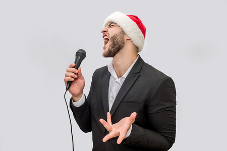 Adult singer singing song in microphone. He screams and moves with hand. Young man wears suit and Christmas hat. Isolated on white background.